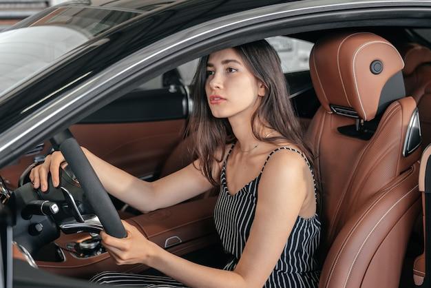 Jovem mulher asiática sentada em um carro de luxo na garagem antes de ligar o motor