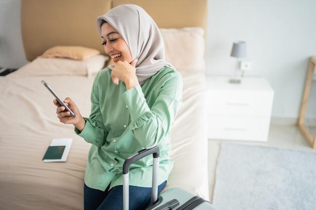 Jovem mulher asiática, sentada na cama segurando seu handphone e mala