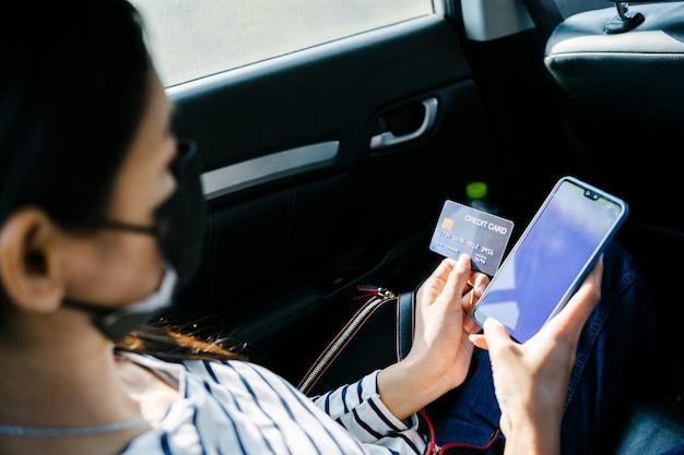 Jovem mulher asiática sentada no banco de trás do carro e usando o celular e segurando o cartão de crédito nas mãos.