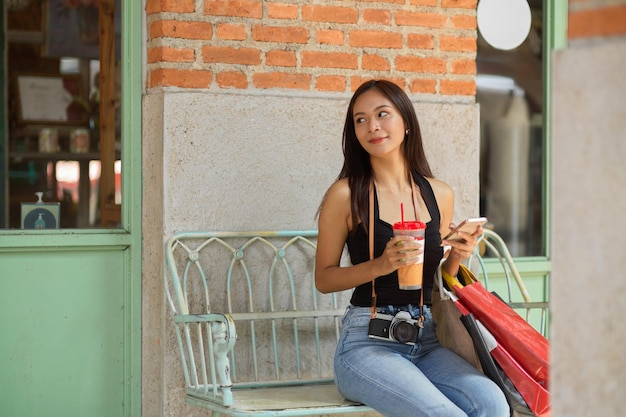 Jovem mulher asiática sentada no banco em frente à cafeteria segurando sacolas de compras smartphone