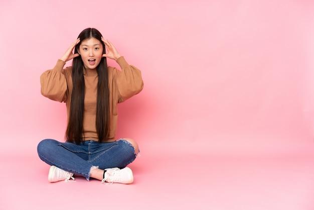 Jovem mulher asiática, sentada no chão na parede rosa com expressão de surpresa