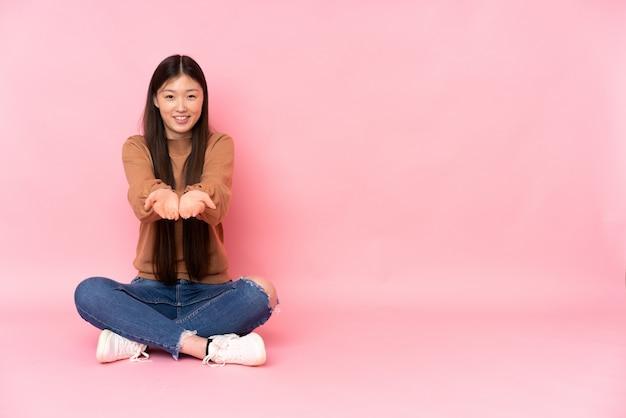 Jovem mulher asiática, sentada no chão na parede rosa segurando o espaço em branco na palma da mão