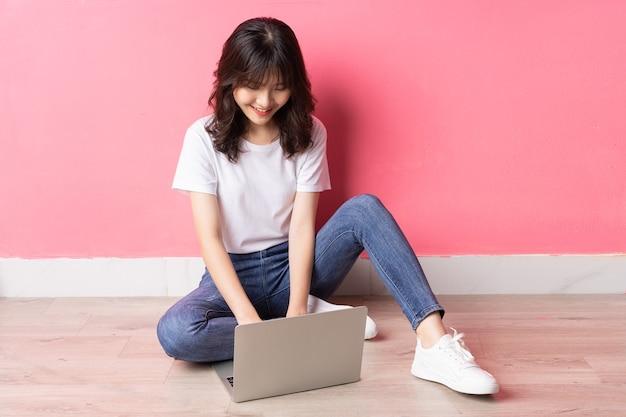 Jovem mulher asiática sentada no chão usando um laptop