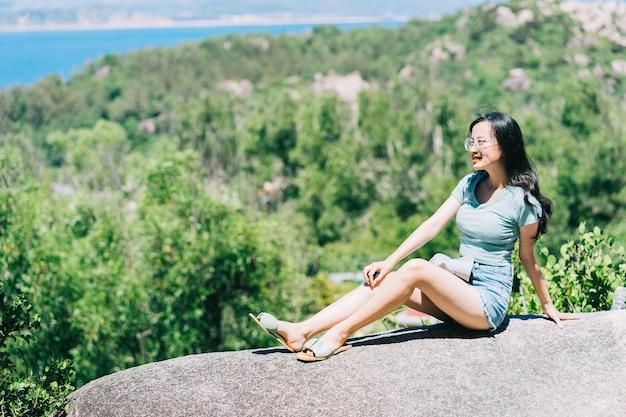 Jovem mulher asiática sentada numa pedra no verão