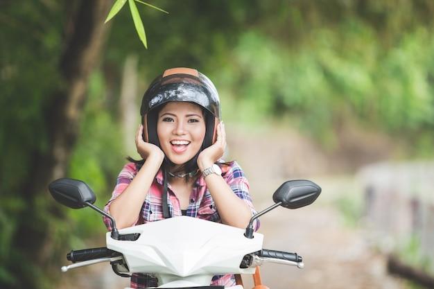 Jovem mulher asiática, sentado em uma motocicleta em um parque, ambos mão h