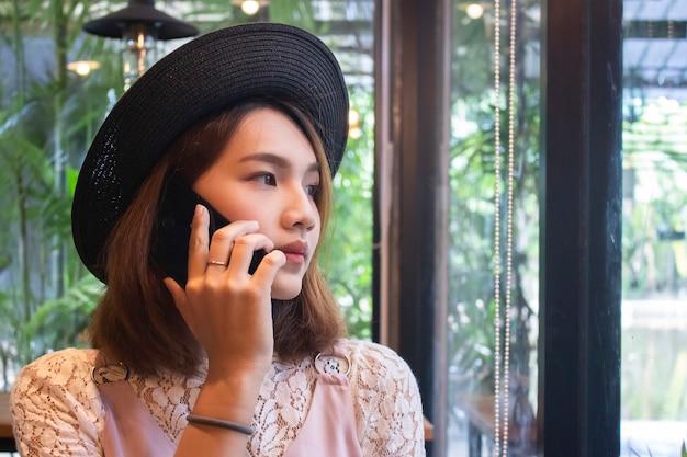 Jovem mulher asiática sentado no café e falar ao telefone