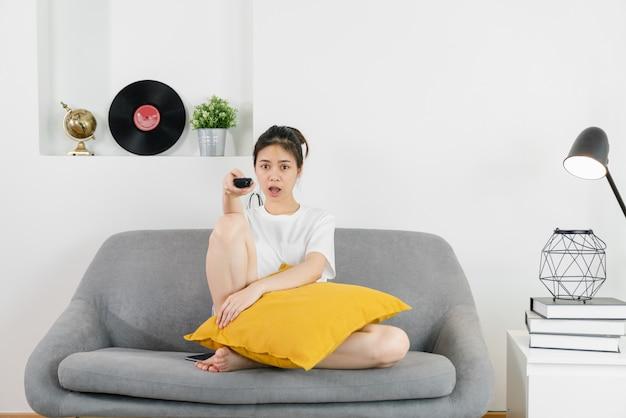 Jovem mulher asiática, sentado no sofá da casa e segurando o controle remoto da tv para assistir filmes em um dia relaxante.