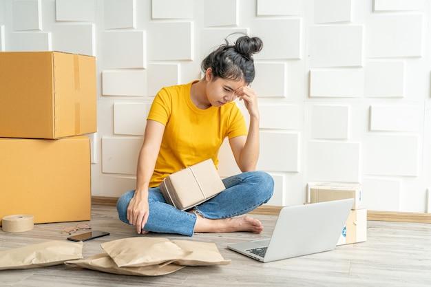 Jovem mulher asiática sentindo estresse ou deprimir na frente de seu laptop