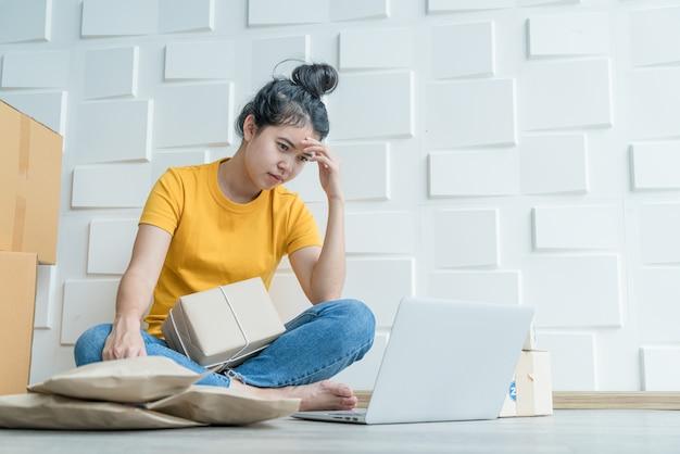 Jovem mulher asiática, sentindo o estresse na frente de seu laptop