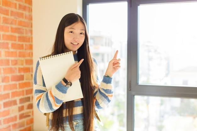 Jovem mulher asiática sentindo-se alegre e surpresa, sorrindo com uma expressão chocada e apontando para o lado