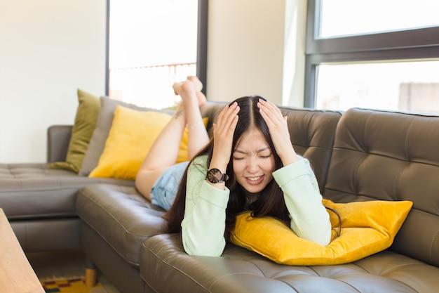 Jovem mulher asiática sentindo-se estressada e frustrada, levando as mãos à cabeça, sentindo-se cansada, infeliz e com enxaqueca