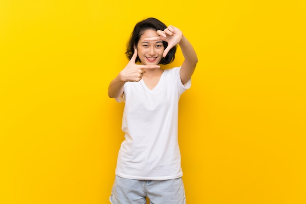 Jovem mulher asiática sobre a cara de focalização isolada da parede amarela. símbolo de enquadramento