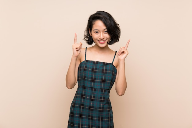 Jovem mulher asiática sobre a parede amarela isolada que aponta acima de uma grande ideia