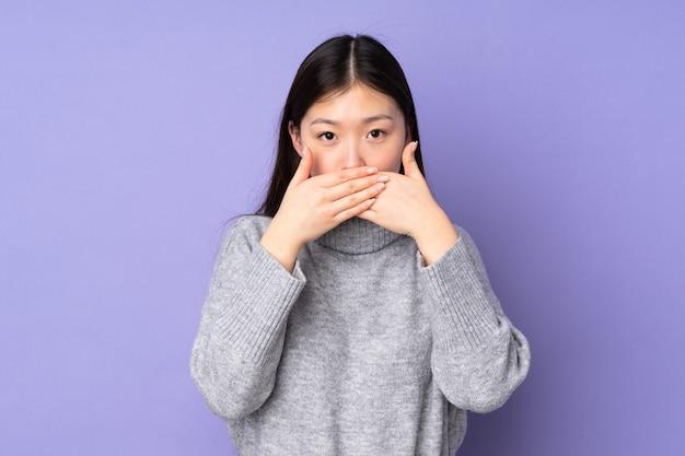 Jovem mulher asiática sobre fundo isolado cobrindo a boca com as mãos