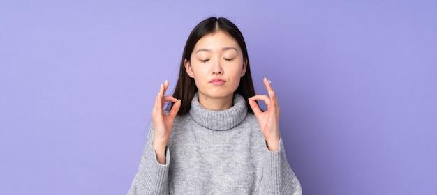 Jovem mulher asiática sobre fundo isolado em pose zen