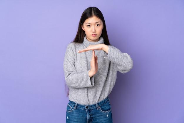 Jovem mulher asiática sobre fundo isolado fazendo um gesto de pausa