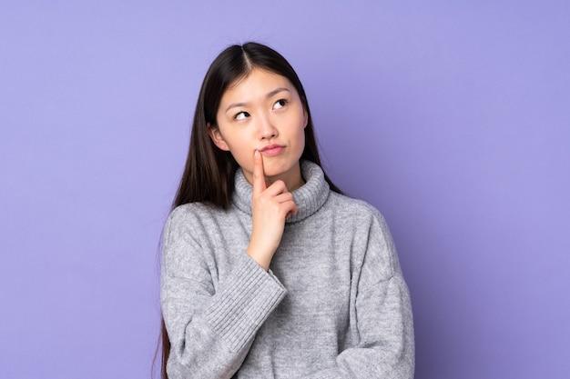Jovem mulher asiática sobre fundo isolado tendo dúvidas enquanto olha para cima
