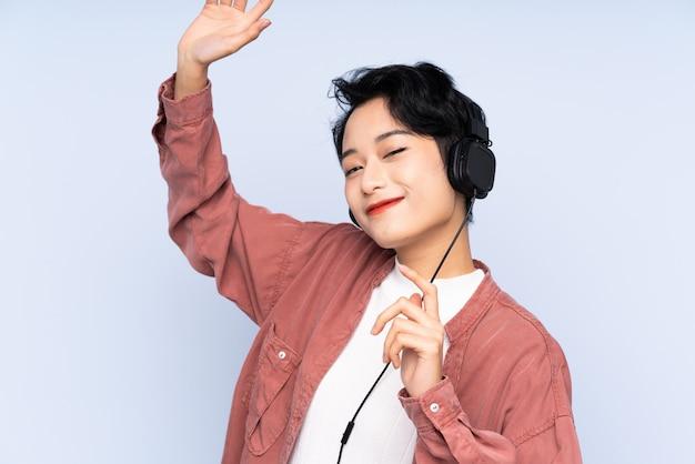 Jovem mulher asiática sobre música e parede azul isolada ouvindo e dançando
