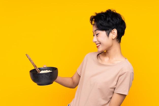 Jovem mulher asiática sobre parede amarela isolada com expressão feliz, mantendo uma tigela de macarrão com pauzinhos