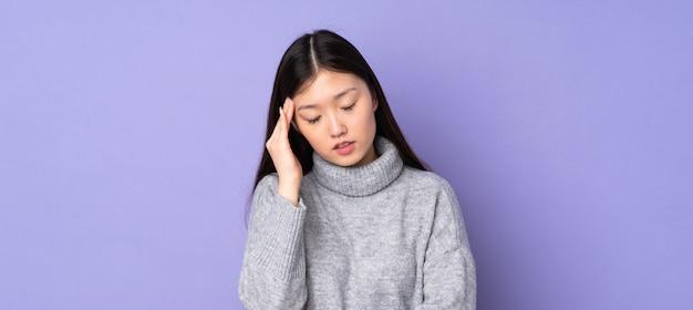 Jovem mulher asiática sobre parede com dor de cabeça