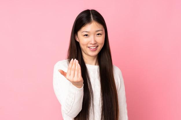 Jovem mulher asiática sobre parede convidando para vir com a mão