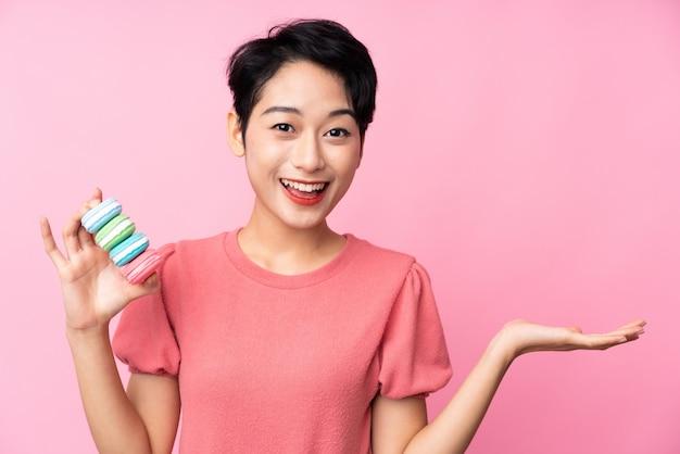 Jovem mulher asiática sobre parede rosa isolada segurando macarons franceses coloridos com expressão chocada
