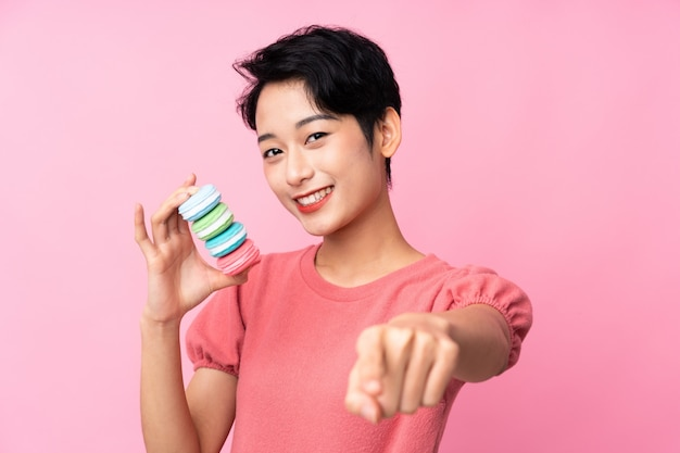 Jovem mulher asiática sobre parede rosa isolada segurando macarons franceses coloridos e aponta o dedo para você