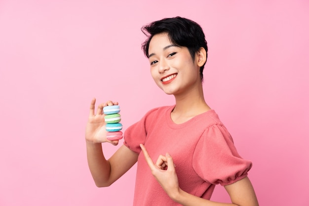 Jovem mulher asiática sobre parede rosa isolada segurando macarons franceses coloridos e apontando-o