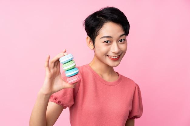 Jovem mulher asiática sobre parede rosa isolada segurando macarons franceses coloridos e com expressão feliz