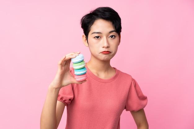 Jovem mulher asiática sobre parede rosa isolada segurando macarons franceses coloridos e com expressão triste