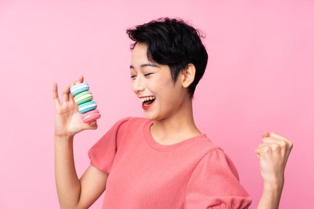 Jovem mulher asiática sobre parede rosa isolada segurando macarons franceses coloridos e comemorando uma vitória