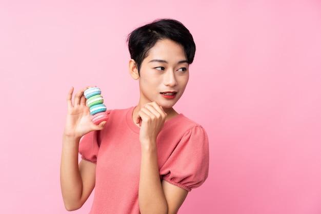 Jovem mulher asiática sobre parede rosa isolada segurando macarons franceses coloridos e pensando uma idéia