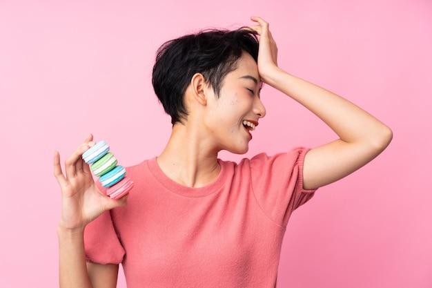 Jovem mulher asiática sobre parede rosa isolada segurando macarons franceses coloridos e pretendendo a solução