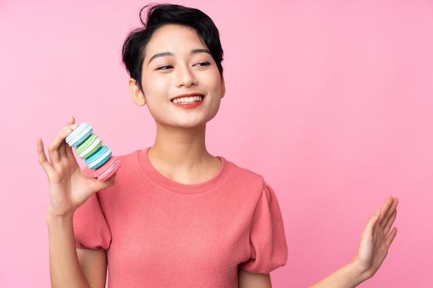 Jovem mulher asiática sobre parede rosa isolada segurando macarons franceses coloridos e saudação