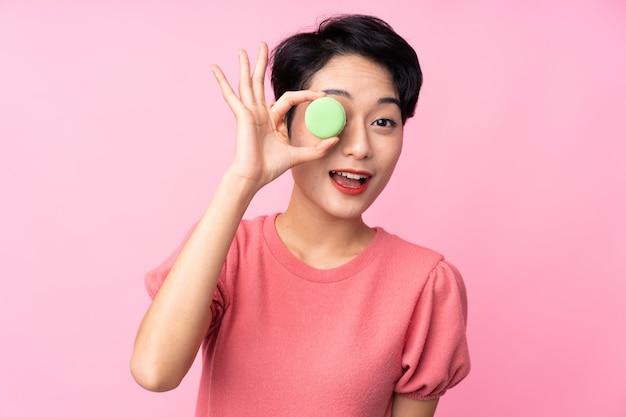 Jovem mulher asiática sobre parede rosa isolada segurando macarons franceses coloridos