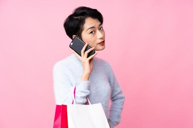 Jovem mulher asiática sobre parede rosa isolada segurando sacolas de compras e chamando um amigo com seu telefone celular