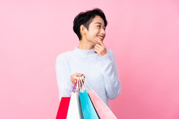 Jovem mulher asiática sobre parede rosa isolada segurando sacolas de compras e pensando