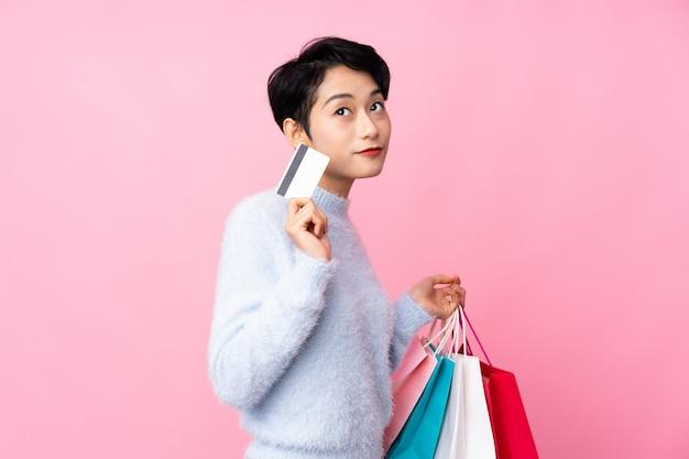 Jovem mulher asiática sobre parede rosa isolada segurando sacolas de compras e um cartão de crédito e pensando