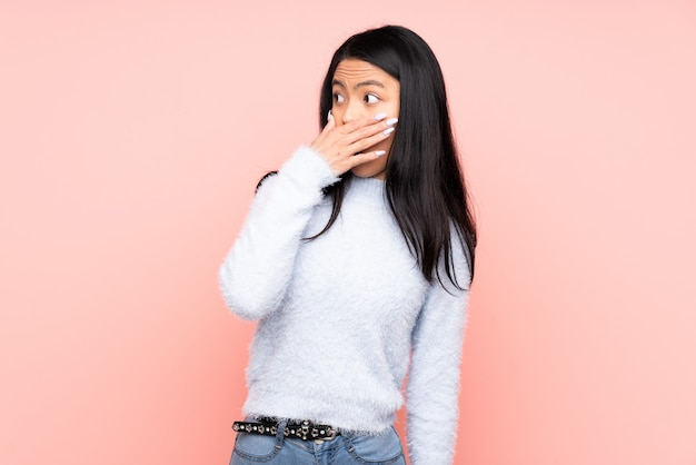 Jovem mulher asiática sobre parede rosa