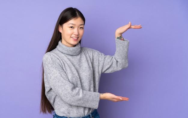 Jovem mulher asiática sobre parede segurando espaço em branco