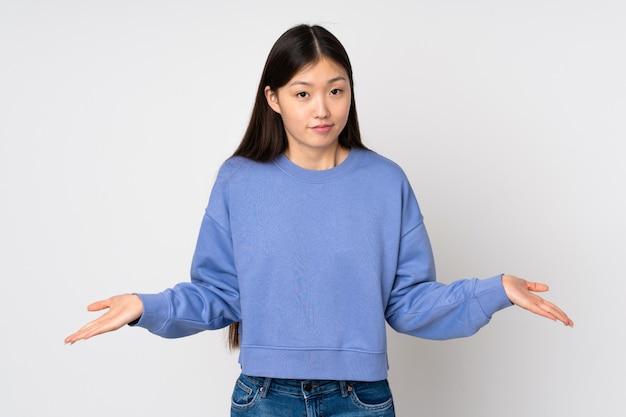 Jovem mulher asiática sobre parede tendo dúvidas
