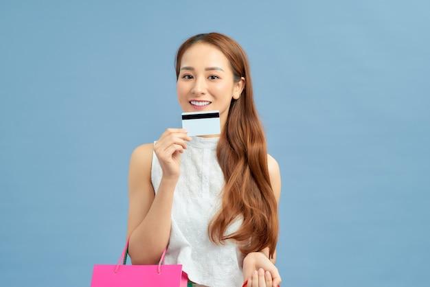 Jovem mulher asiática sobre um fundo azul isolado segurando sacolas de compras e um cartão de crédito