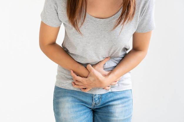 Jovem mulher asiática sofrendo de dor de estômago isolada no branco, estúdio tiro