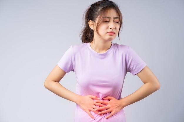 Jovem mulher asiática sofrendo de gastrite