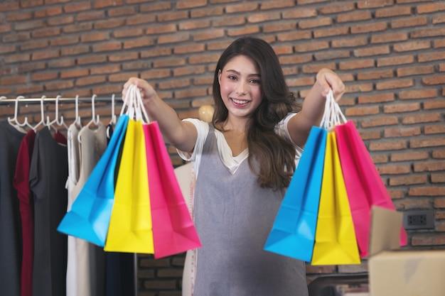 Jovem mulher asiática sorri com sucesso pme e sacola de compras na mão para fazer compras online em casa.