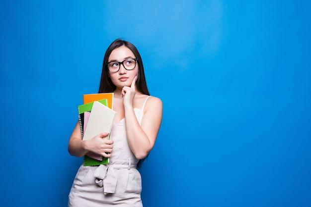 Jovem mulher asiática sorri e tem livros nas mãos. conceito de educação, faculdade, sessão, exame.