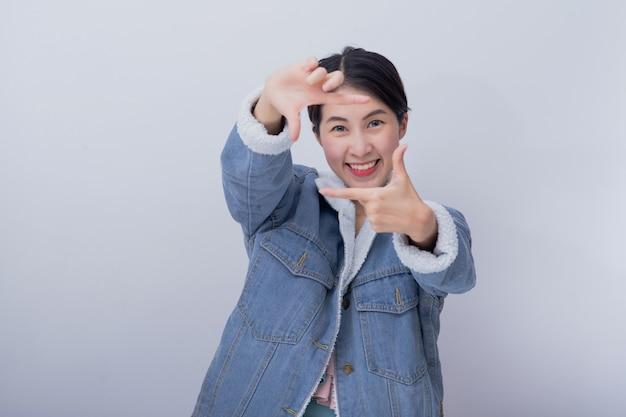 Jovem mulher asiática sorridente animado, mostrando a mão com expressão sentimento surpreso e espantado, menina caucasiana positiva, vestindo roupas casuais azuis