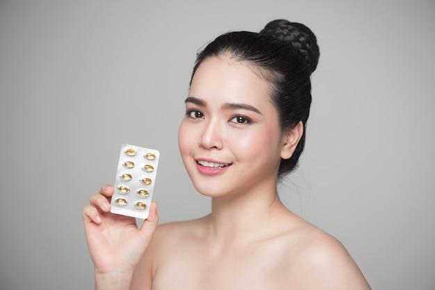 Jovem mulher asiática sorridente com cápsula de óleo de peixe omega 3