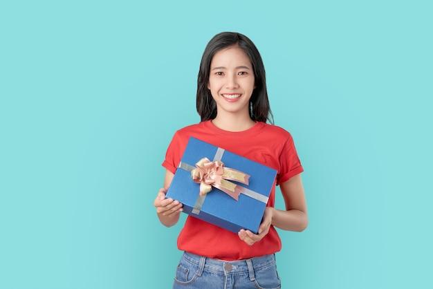 Jovem mulher asiática sorridente em t-shirt vermelha segurando presente azul sobre fundo claro.