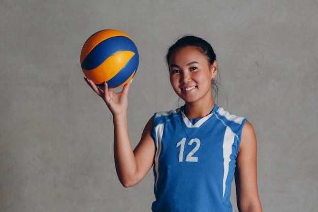 Jovem mulher asiática sorridente jogador de voleibol de uniforme azul com bola